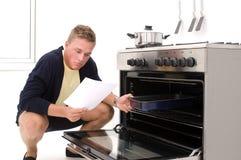 Hombre joven desorientado en cocina Imagen de archivo