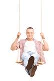 Hombre joven despreocupado que balancea en un oscilación Imagen de archivo