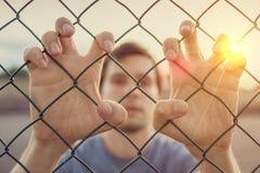Hombre joven detrás de la cerca atada con alambre Concepto de la inmigración imágenes de archivo libres de regalías