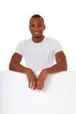 Hombre joven detrás de la muestra blanca en blanco Fotografía de archivo libre de regalías