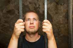Hombre joven detrás de las barras Imagen de archivo libre de regalías