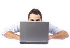 Hombre joven detrás de una computadora portátil Imagen de archivo libre de regalías