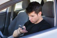Hombre joven distraído que usa el teléfono celular mientras que fotos de archivo