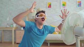 Hombre joven divertido con el fan eléctrico que goza del aire fresco en su apartamento metrajes