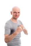 Hombre joven divertido con las manos de la cabeza calva y del puño Imagen de archivo