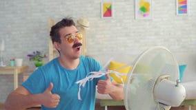 Hombre joven divertido delante de escapes de trabajo de una fan eléctrica del calor en el apartamento MES lento almacen de metraje de vídeo