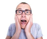 Hombre joven divertido en vidrios con los apoyos en los dientes que grita el isolat Imagen de archivo libre de regalías