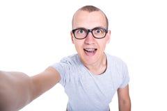 Hombre joven divertido en vidrios con los apoyos en los dientes que toman el selfie pH Fotos de archivo
