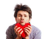 Hombre joven divertido lindo con el corazón del juguete Foto de archivo
