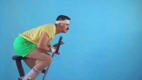 Hombre joven divertido a partir de los años 80 con un bigote y los vidrios en la bicicleta estática en un fondo azul MES lento metrajes
