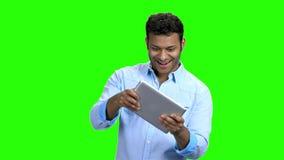 Hombre joven divertido que juega al juego en la tableta del ordenador almacen de video