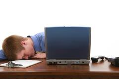 Hombre joven dormido en el escritorio Imágenes de archivo libres de regalías