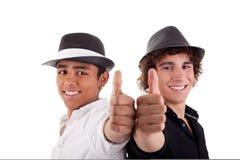 Hombre joven dos de diversos colores, con el pulgar para arriba Fotos de archivo libres de regalías