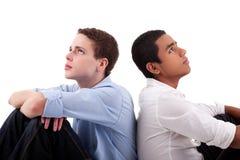 Hombre joven dos de diversos colores, sentándose en suelo Fotografía de archivo libre de regalías
