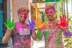 Hombre joven dos que muestra las manos pintadas coloridas durante el festival de Holi en la India imagenes de archivo