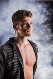 Hombre joven duro hermoso en sudadera con capucha oscura en ahumado Fotos de archivo libres de regalías