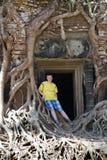 Hombre joven, el adolescente en una entrada a destruida cubierto con las raíces del templo Prasat Chrap de los árboles en los com Foto de archivo libre de regalías