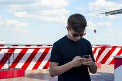 Hombre joven elegante con el teléfono en el tejado del edificio Imagen de archivo