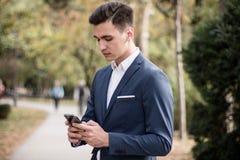 Hombre joven elegante con smartphone en el parque Foto de archivo