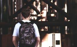 Hombre joven elegante con una mochila en el suyo detrás Fotos de archivo libres de regalías