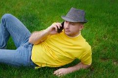 Hombre joven elegante en una camiseta amarilla con el teléfono en la hierba Foto de archivo libre de regalías