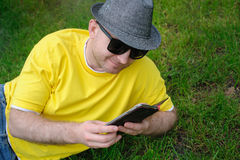 Hombre joven elegante en una camiseta amarilla con el teléfono en la hierba Imágenes de archivo libres de regalías