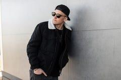 Hombre joven elegante moderno del inconformista en una chaqueta negra elegante en un casquillo de moda en gafas de sol oscuras de foto de archivo libre de regalías