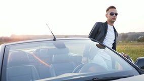 Hombre joven elegante que abre la puerta de coche y que se sienta en cabriolé metrajes