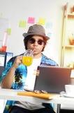 Hombre joven elegante que bebe a Juice While Working anaranjado el verano Imagenes de archivo