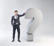 Hombre joven elegante que se inclina contra el signo de interrogación imagenes de archivo
