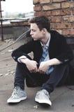 Hombre joven elegante que se sienta en el tejado de un edificio Fotos de archivo libres de regalías