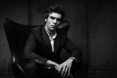 Hombre joven elegante que se sienta en una silla Chaqueta negra y camisa blanca fotos de archivo