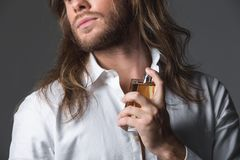 Hombre joven elegante que usa perfume imagen de archivo