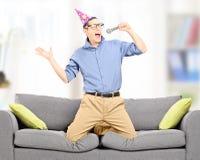 Hombre joven emocionado con el sombrero del partido que canta en un micrófono Fotos de archivo libres de regalías