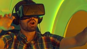 Hombre joven emocionado que disfruta de la atracción de la realidad virtual Imágenes de archivo libres de regalías