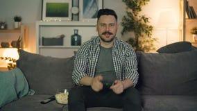 Hombre joven emocionado que juega al videojuego en casa en la noche que gana mostrando los pulgares-para arriba almacen de metraje de vídeo