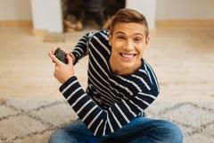 Hombre joven emocionado que juega a un juego Imagen de archivo libre de regalías