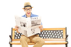Hombre joven emocionado que lee un periódico asentado en banco Imágenes de archivo libres de regalías