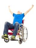 Hombre joven emocionado que se sienta en una silla de ruedas y que aumenta las manos Fotografía de archivo libre de regalías