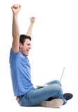 Hombre joven emocionado que usa la computadora portátil foto de archivo libre de regalías