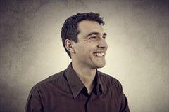 Hombre joven emocionado sonriente aislado en fondo gris fotografía de archivo libre de regalías