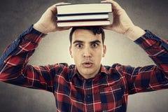 Hombre joven emocionado sonriente con los libros en su cabeza fotos de archivo libres de regalías