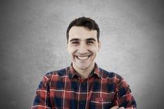 Hombre joven emocionado sonriente en un fondo gris fotos de archivo