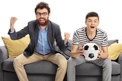 Hombre joven emocionado y un fútbol de observación del adolescente Fotos de archivo