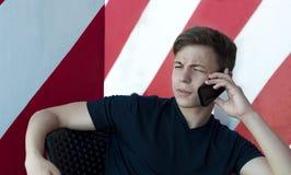 Hombre joven emocional que habla en el teléfono Imagen de archivo libre de regalías