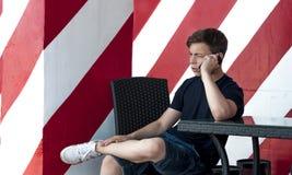 Hombre joven emocional que habla en el teléfono Imagen de archivo