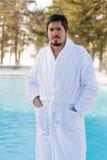 Hombre joven en albornoz cerca de la piscina al aire libre en el invierno Imagenes de archivo