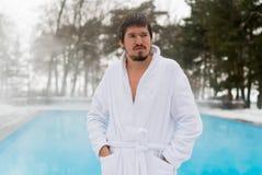 Hombre joven en albornoz cerca de la piscina al aire libre en el invierno Fotografía de archivo libre de regalías