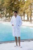 Hombre joven en albornoz cerca de la piscina al aire libre en el invierno Imágenes de archivo libres de regalías
