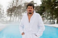 Hombre joven en albornoz cerca de la piscina al aire libre en el invierno Imagen de archivo libre de regalías